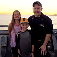 Brian Bailey and his two children on a Navy ship with the sun setting in the background