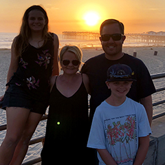 Brian Bailey with his wife and two children with a sunset in the background.