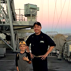 Brian Bailey and his son on a Navy ship with the sun setting in the background